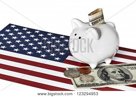 White ceramic piggy bank with one quarter a nickel and a penny on top of a US one hundred dollar bill with an American flag isolated on white