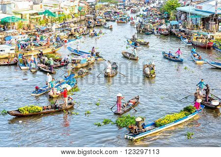 Soc Trang, Vietnam - February 3rd, 2016: Sunny on floating market with hundreds of large and small boats concentrate on agricultural trade rivers, flowers, fruits bustling sunny morning in Soc Trang, Vietnam