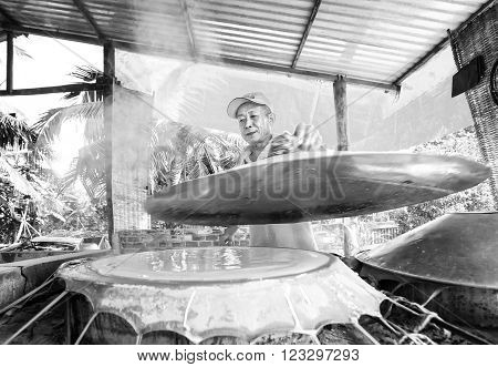 Can Tho, Vietnam - February 4th, 2016: Joy craftsmen noodle cake coated with skillful hands coated with real bread and cover tightly round the bread in oven cooked in the countryside Can Tho, Vietnam