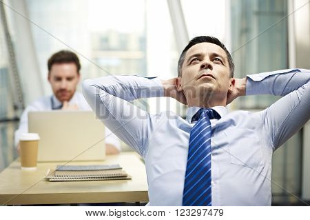 caucasian businessman sitting in office hands behind head thinking with colleague working in background.