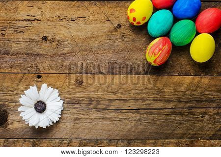 Easter eggs in a box and flower on old wooden background