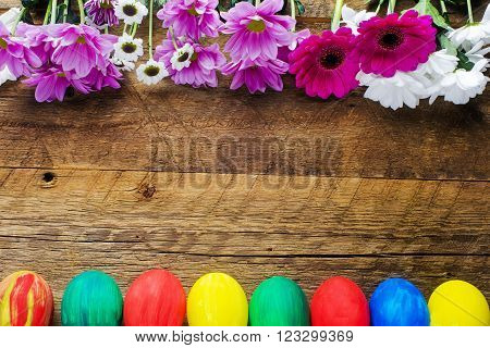 Easter eggs and flowers frame on a wooden background