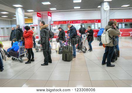 SHEREMETYEVO, RUSSIA - March 18, 2016: Passengers wait a train near the cashdesks of aeroexpress in an airport.