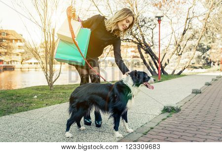 Fashionable woman and her border collie dog going shopping in the city center