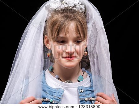 Teen girl trying on a wedding veil. The concept of early marriage, dreams of a wedding.