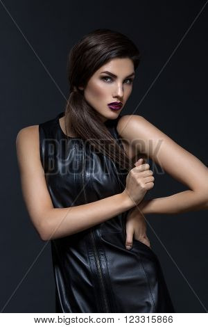 Beautiful young woman with dark lips and ponytail in fancy leather dress over black background. Copy space.