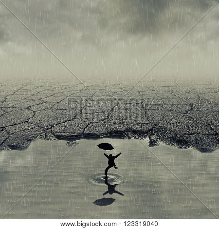 Surrealistic image with a boy jumping in a pothole of cracked asphalt in a rainy day. Broken pavement with a dirty water puddle in a imaginary town.