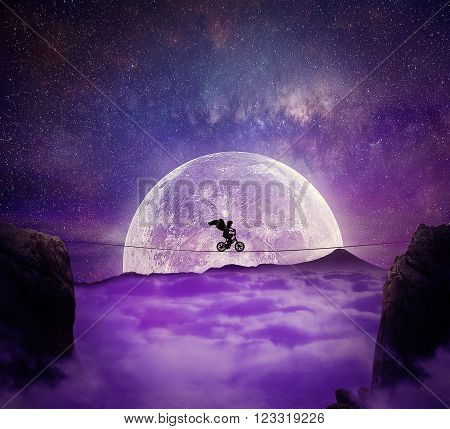 Boy with angel wings balance on a wire over a chasm riding a bicycle. Self overcoming and risk taking concept. Full moon night background over the clouds