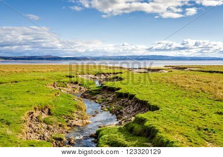Coastline by green fields at Grange-over-sands in Cumbria, England with blue skies and sunshine.