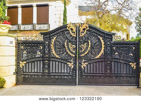 Beverly Hills, CA, USA - January 16, 2016: Beverly Hills Old beautiful wrought iron gates in stone colons. Entrance to palace.