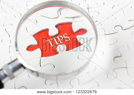 Tips word with magnifying glass over jigsaw puzzle.