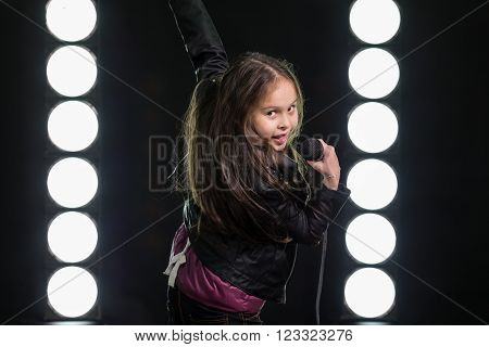 Young rock star with mic on stage with stagelights behind her