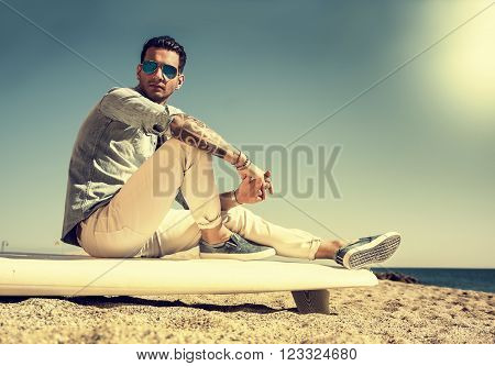 Stylish handsome young man in mirrored sunglasses sitting on surfboard on beach in sunlight