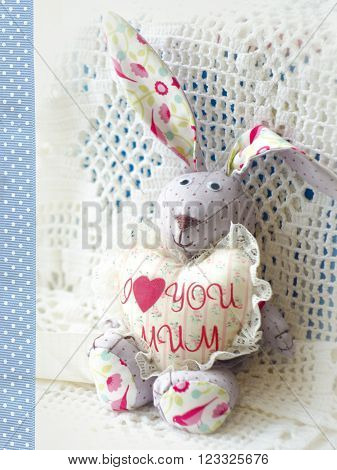 Cute hare. Happy Mother's Day bunnie holding heart with the inscription I love mum. Greeting card for Mother's day. Holday toys.