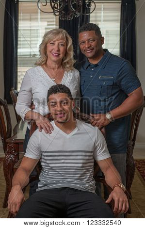 Closer view of handsome son seated with his multi-racial family.