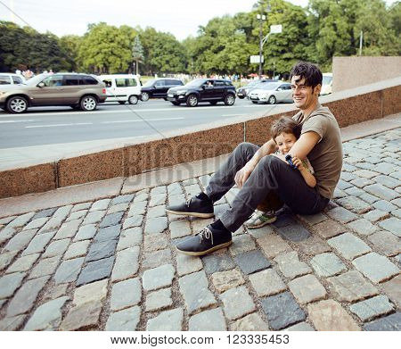 little son with father outside hagging and smiling, city lifestyle concept, parks and cars