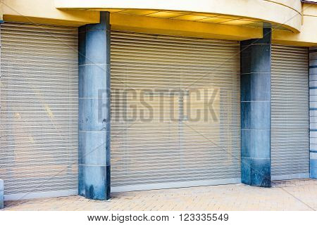 Metal netting as safety measure in front of closed shopping mall. This retractable device makes it harder for criminals to enter or vandalize the place.