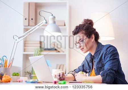 Beautiful young woman is searching information in the internet. She is typing on the laptop and looking at the screen with interest. The lady is sitting at desk and holding an apple