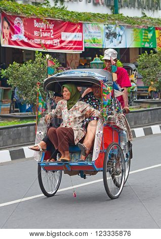 YOGYAKARTA - AUGUST 03: Traditional rikshaw transport on streets of Yogyakarta, Java, Indonesia on August 03, 2010. Bicycle rikshaw remains popular means of transport in many Indonesian cities.