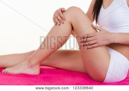 Legs and hands of the woman on a pink floor