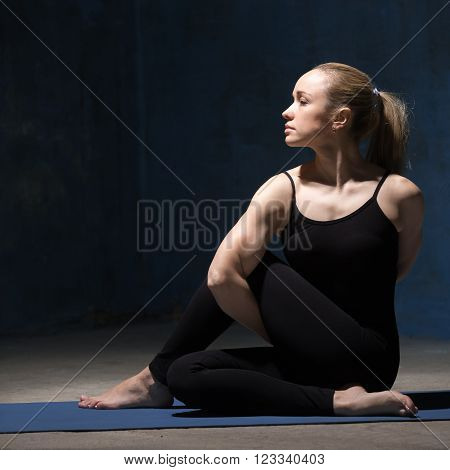Portrait of beautiful sporty fit young woman in black sportswear working out against grunge dark blue wall indoors. Model sitting in variation of ardha matsyendrasana. Square image. Copy space