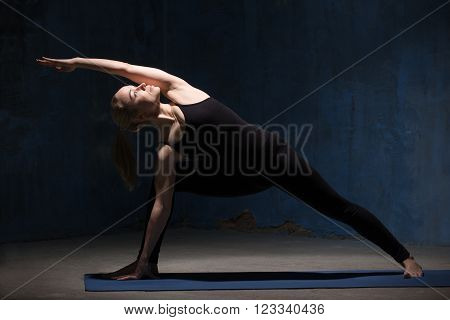 Beautiful sporty fit young woman in black sportswear working out indoors against grunge dark blue wall. Model standing in Extended Side Angle posture, Utthita Parsva Konasana. Full length