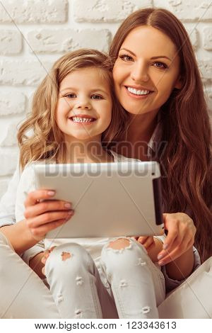 Beautiful young mother and her cute little daughter are listening to music using a smart phone and smiling against white brick wall