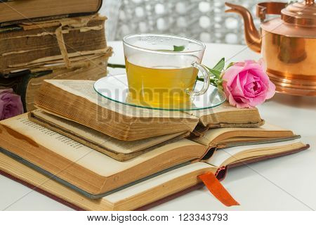 Cup of tee in glass with old books and rose flower