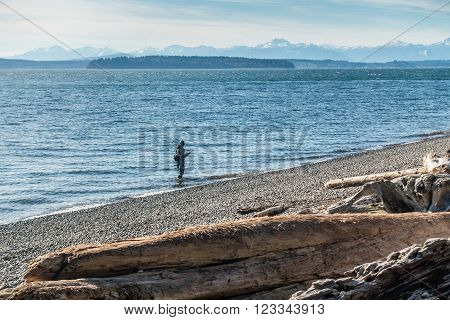 A view of a fisherman and the Olympic Mountains from Lincoln Park in West Seattle Washington.