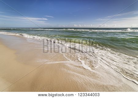 Beach at Gulf Islands National Seashore in Pensacola Florida showing incoming surf waves clean sandy beach