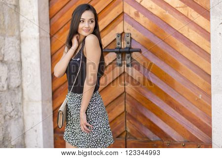 Pretty young woman standing in front of the door