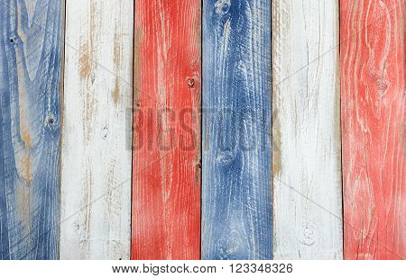 Stressed wooden boards painted red white and blue for patriotic concept of United States of America. Layout in vertical format.