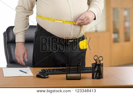 Standing man measures his waist with yellow tape meter at office desk
