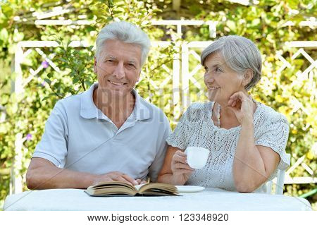 Beautiful happy old couple with drink and book in summer