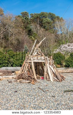 A hut made from driftwood stands on the shore at Lincoln Park in West Seattle Washington.