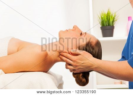 Masseur doing neck massage on woman laying on couch in the spa salon