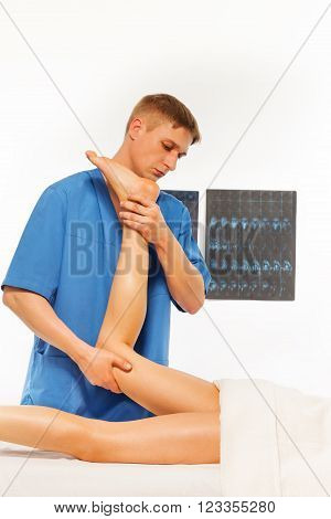 Physical therapist doing massage and exercises on woman leg