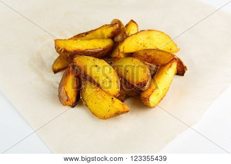 Fried Potato wedges. Natural and organic food from farm. Delicious crispy baked potato wedges closeup at white background. Roasted potato wedges. Closeup at white plate background. Horizontal image