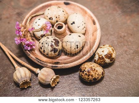 quail eggs are in the earthen plate with flower and dead poppy