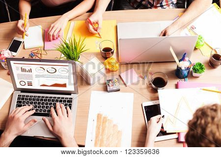 Close up of arms of cheerful creative team is working on a project together. They are using a laptop and writing down their ideas. The men and women are sitting at the desk