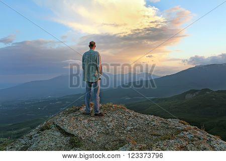A man stands on top of the evening and looking at the village beneath the mountain. Man sees the approach of change and thunderstorms. human fear of the unknown future