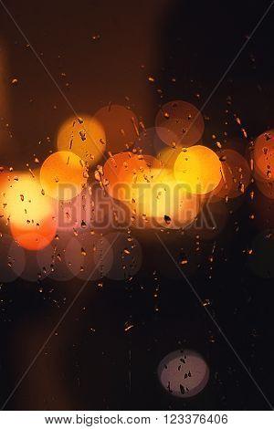 Drop of rain on window with city bokeh lighs