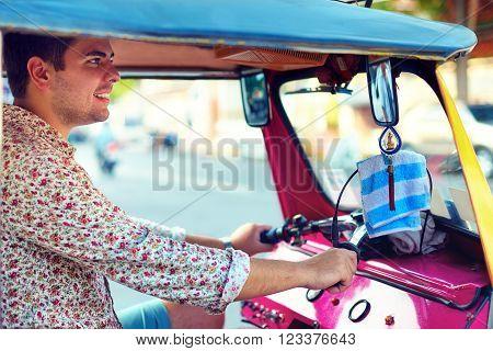 young adult man drives traditional asian transport tuk-tuk