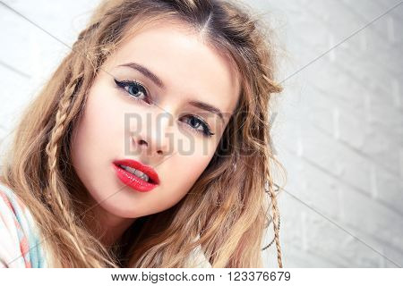 Boho Girl Close-Up Portrait at White Brick Wall Background. Bohemian Fashion Woman Portrait. Toned Photo with Copy Space.