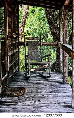 Looking across old wooden porch towards an empty rocking chair with wicker back in tropical estero florida setting.