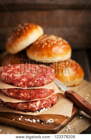Raw ground beef meat steak cutlets and burger buns on wooden background ready for cooking