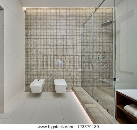 Shower room in a modern style. Back wall decorated with beige mosaic. On the back wall there is a white bidet, white toilet and switches. On the right there is a shower cabin with beige textured tiles on the floor. On the side walls and floor there are li