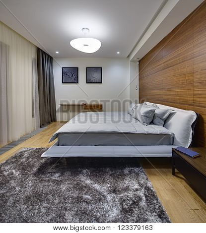 Bedroom in a modern style with light walls. There is a big bed with gray bedcover and pillows. On the right side of the bed there is a dark wooden table with a book. On the right wall there is a big niche with wooden panel and hanging lamp. On the back wa