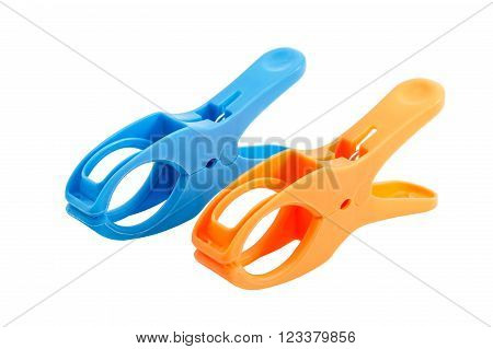 Closeup of two plastic spring clamps (Blue,  Orange) isolated over white background.