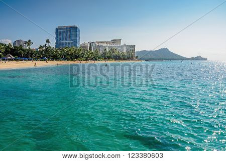 Waikiki, Honolulu, Hawaii, USA - December 13, 2015: Looking back at the Waikiki Beach area, from out at sea onboard a boat. Some hotels line the skyline, with Diamond Head on the right. Image features the characteristic tropical turquoise water.
